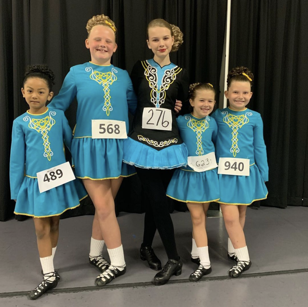 5 Rince Nua Irish dancers smiling, wearing their Digital Feis number cards